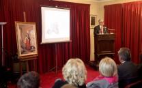 Στο βήμα ο Πρόεδρος του Συλλόγου κ. Ελευθέριος Σκιαδάς. Διακρίνεται ο πίνακας της Ασήμως Λιδωρίκη Γκούρα.